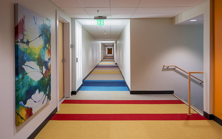 Colorful patterns within the corridors' carpeting provide visual cues for residents with autism.